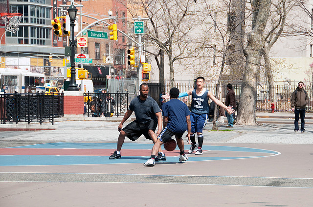 Three young men playing basketball in an urban park