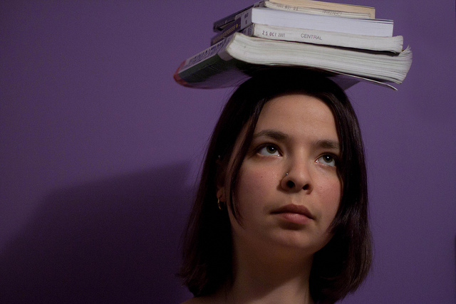 Woman standing against purple wall, with several textbooks balanced on her head