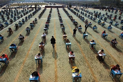 rows of students in desks outdoors, taking an exam. A couple of teachers walk between rows.