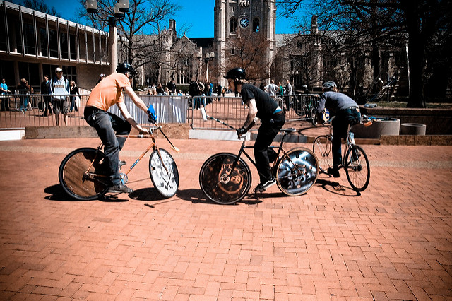 "Three young men playing ""bike polo"" on a brick-paved campus courtyard"