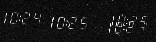 Numbers from a digital clock, blurred, against a black background. From left, 10:24, 10:25, 10:25