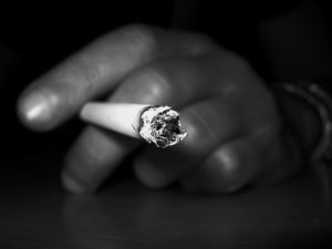 black and white photo of a hand holding a cigarette