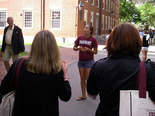 """Campus tour guide wearing a shirt reading 'HAHVAHD"""" gesturing in front of a group of people, in front of a campus building"""