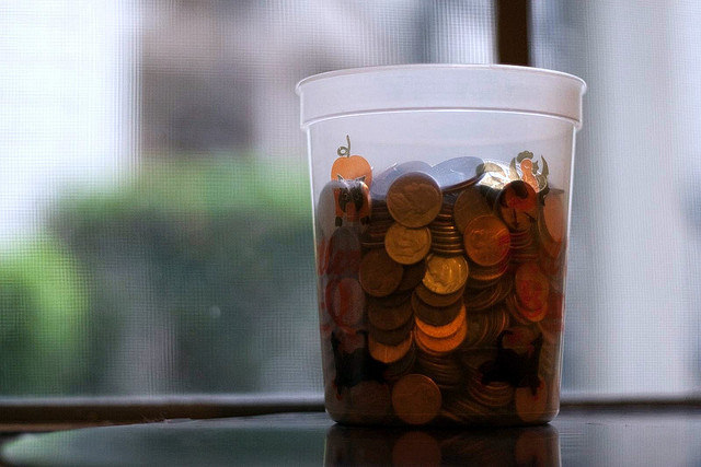 Plastic jar full of pennies sitting in front of a window