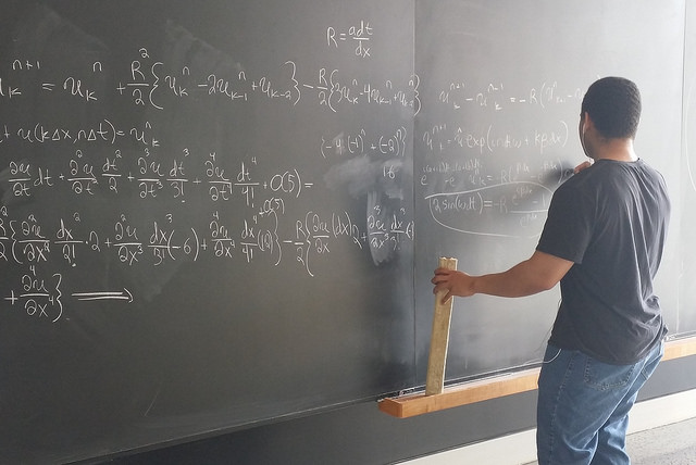 Student working complex math problem on chalkboard