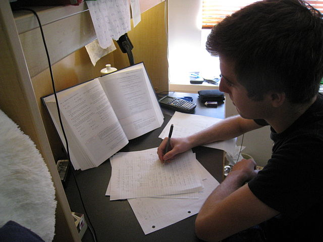 A student taking notes based on his textbook as he reads in the library