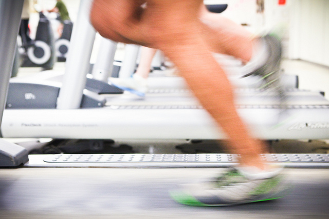 Blurry legs running on a treadmill, with other gym equipment visible in the background