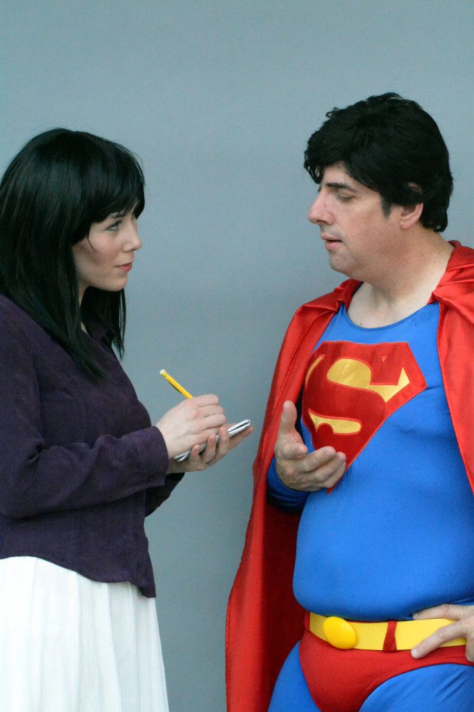 Woman dressed like Lois Lane interviewing a man in a Superman costume