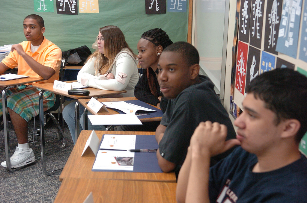 A group of students at desks listening.
