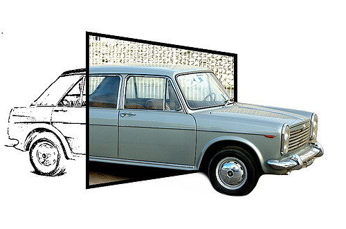 Image of a car emerging through a square set at an angle to the viewer. The front end of the car, outside the square, is a photo-real image of a Renault. The back end, on the other side of the square, is a line drawing of the back part of the car.