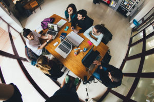 Photo looking down on a group of students around a table, with several open laptops in front of them