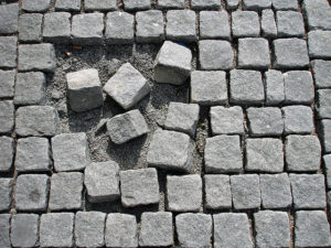 Photo of stone path pavers. Most of them are laid out orderly, but a central cluster are in disarray, with several missing.