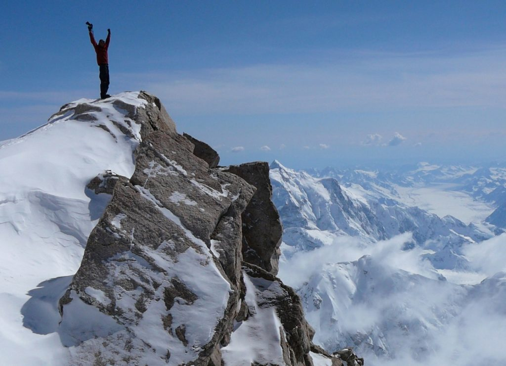 A hiker at the top of a mountain. Other mountain peaks can be seen at lower elevations. The hiker is raising their hands in triumph.