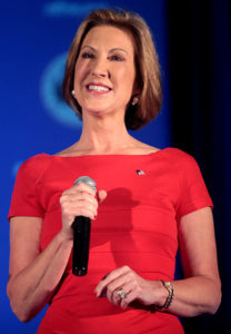 Photo of Carly Fiorina in red dress holding microphone