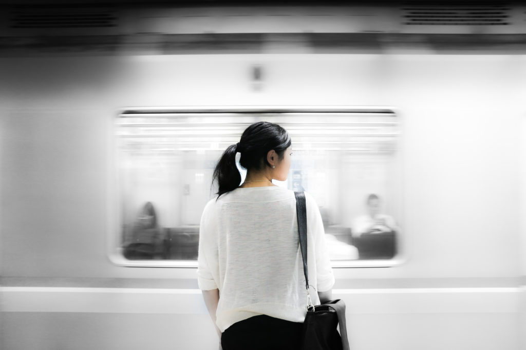 black and white photo of a woman standing in front of a subway as it zips past her.