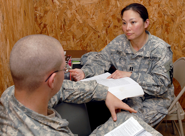 A female captain in the army reads a medical textbook at her desk while conversing with another soldier.