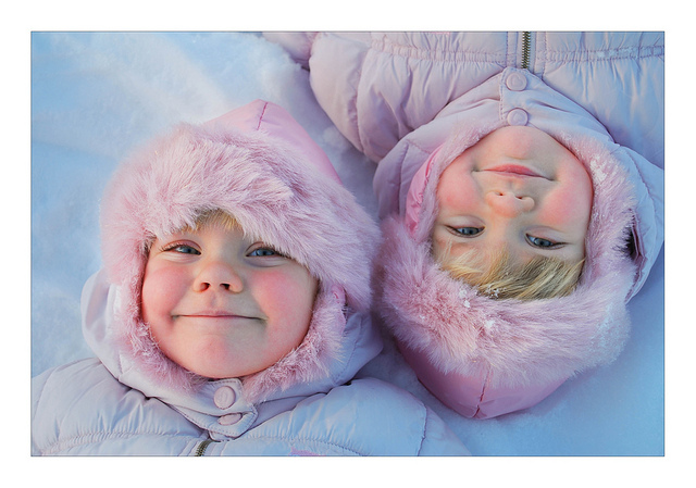 Identical twin toddler girls laying in the snow, wearing pick snowsuits.
