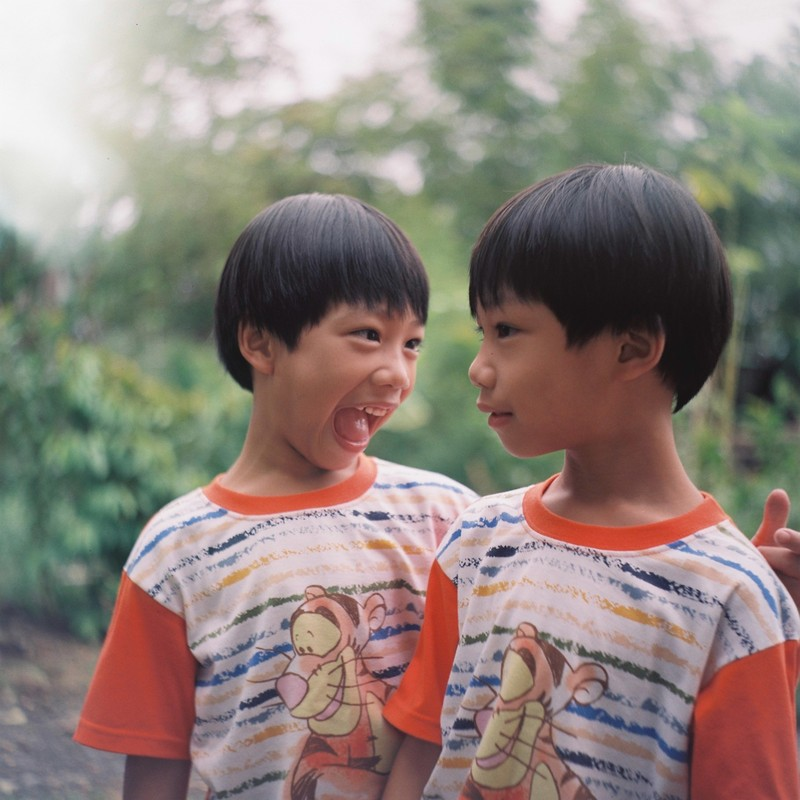 Identical twin boys look at each other, one with a straight face and the other with an open-mouth laugh.