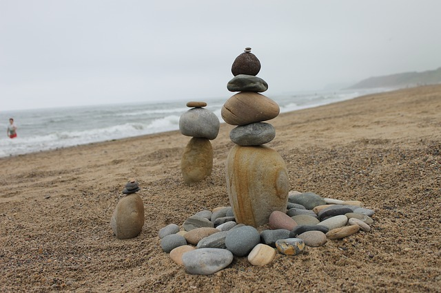 Rocks stacked up like cairns on the beach.
