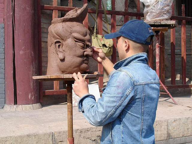 Man working on a sculpture of a face.