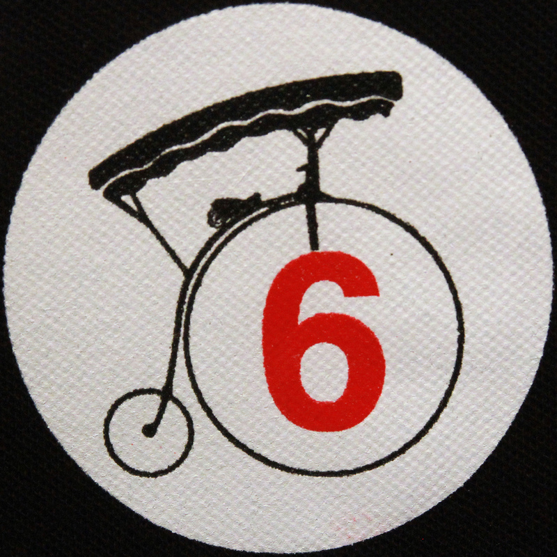 Image of an old bicycle with the large front wheel and the number 6 written in red text inside the wheel.