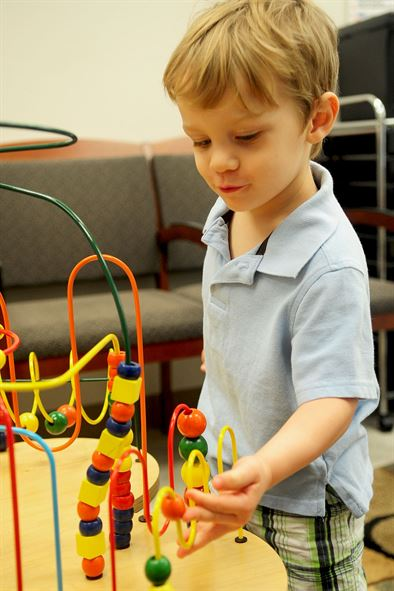 Two year old boy playing with a bead-maze track game in an office waiting room.