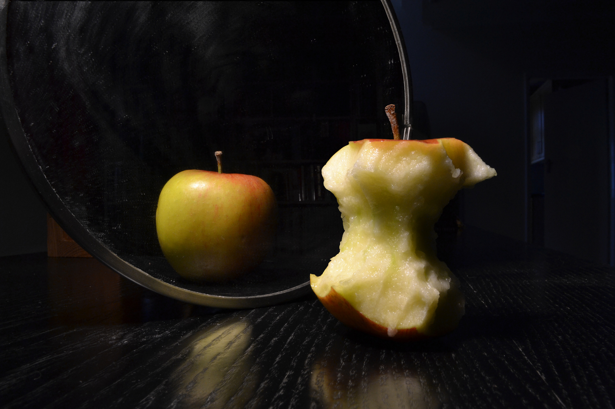 Apple in the mirror. The apple is whole but the reflection is eaten.