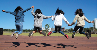 A photograph captures four people midair as they hold hands and jump.