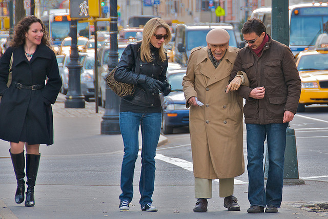 A man walks arm in arm with an elderly man, while another woman approaches as if to offer help as well. Yet another woman walks by smiling at the altruistic behavior.