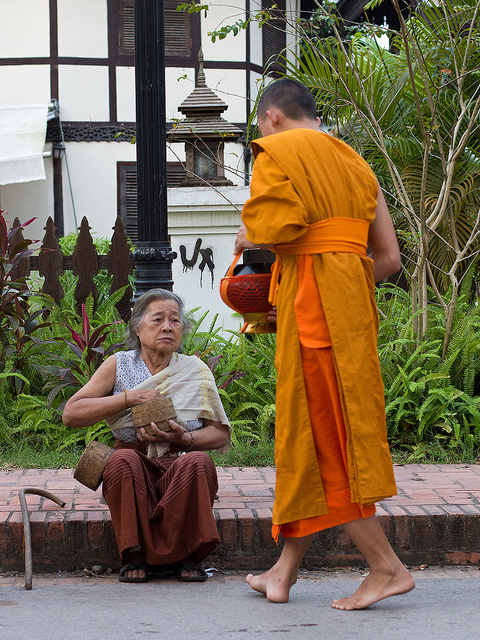 Photo of an older woman sitting on the sidewalk, reaching in her purse to give money to a monk.