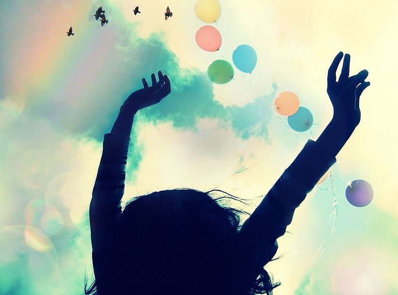 The shadowed outline of a young person with her hands raised in the air while colorful balloons and birds float and fly above.