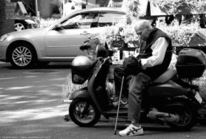 Photograph of an older man holding a cane while getting off of his moped.