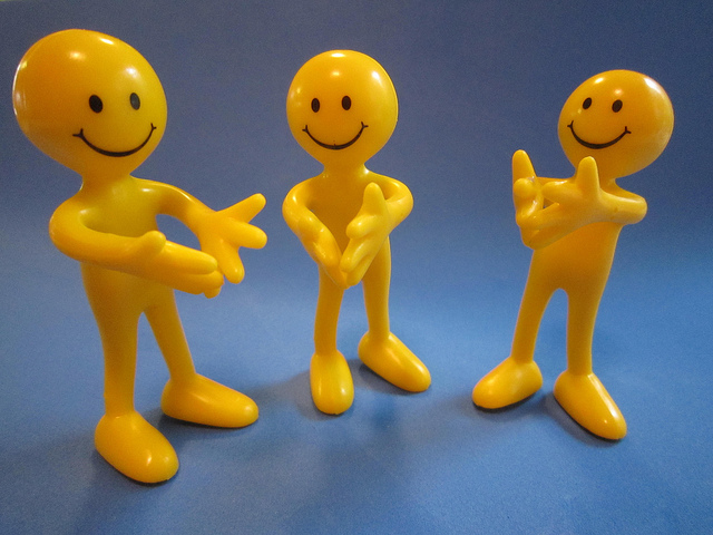 Three toy figures with happy faces clapping their hands.