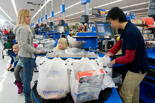 Woman checking out groceries at Walmart.