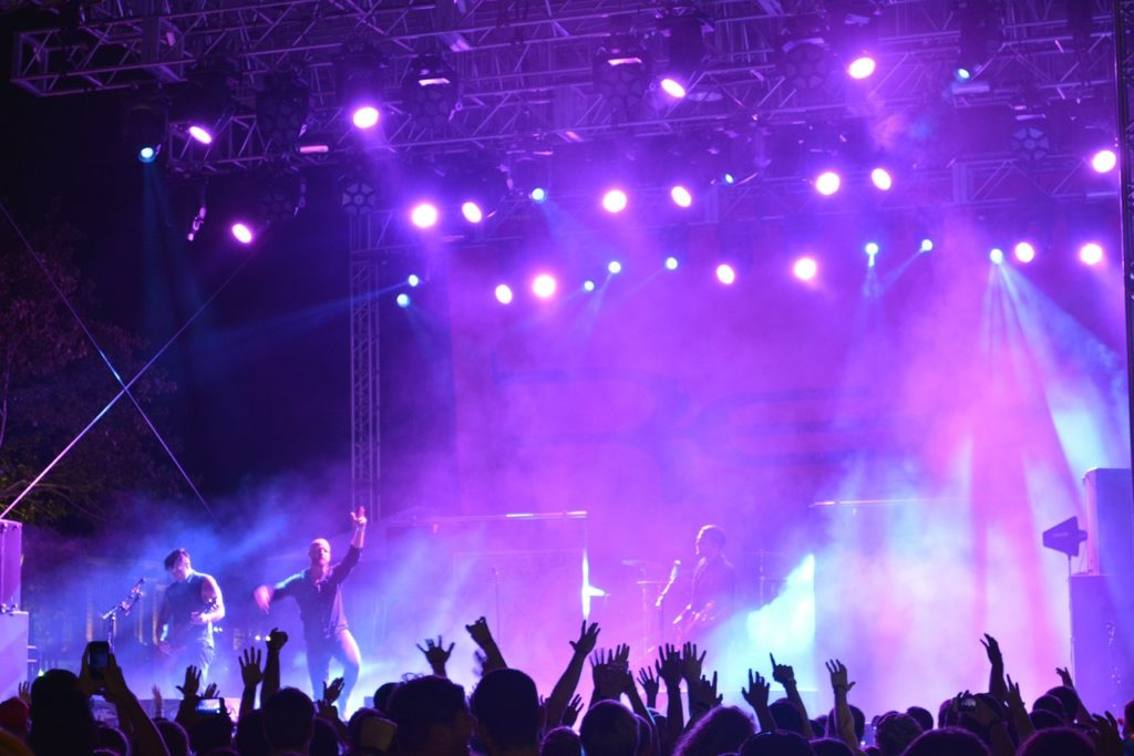Picture from a rock concert. A band plays on the stage with blue and purple lights shining down. Fans raise their hands in the audience.