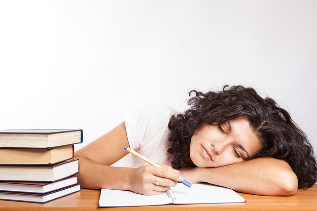 A college students falls asleep on her books while studying.