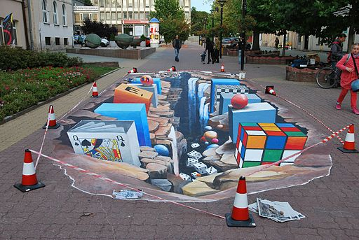 3D street art showing a rubix cube, deck of cards, waterfall, and blocks all on a 2D surface.