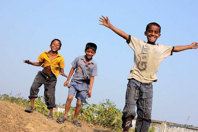 Three young boys playing outside and smiling widely. One boy looks directly at the camera, smiling with his arms outstretched.