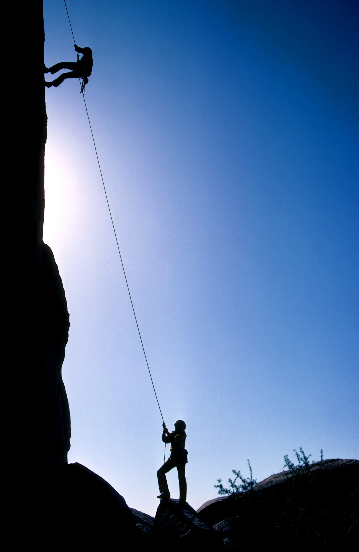 Photo of a man rappeling down a cliff-face while someone belays for him, holding the rope down on the ground.