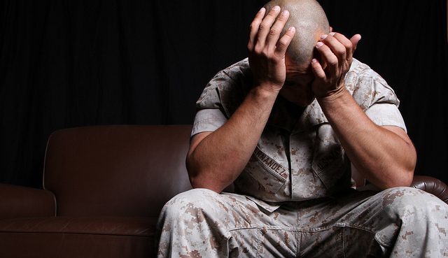 Marine seated with his head in his hands, suffering from PTSD.
