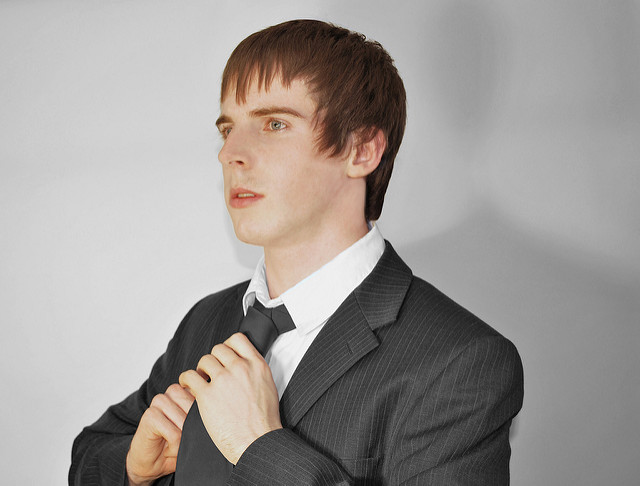 Young man around age 20, adjusting his tie for an interview.