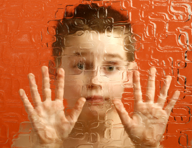 Photograph of an autistic boy looking through a fuzzy glass window with his hands pressed against the glass.