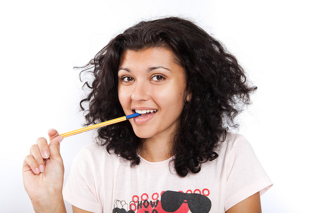 Smiling picture of a college student with a pen in her mouth.