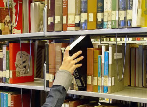 Hand reaching for a book on a bookshelf.