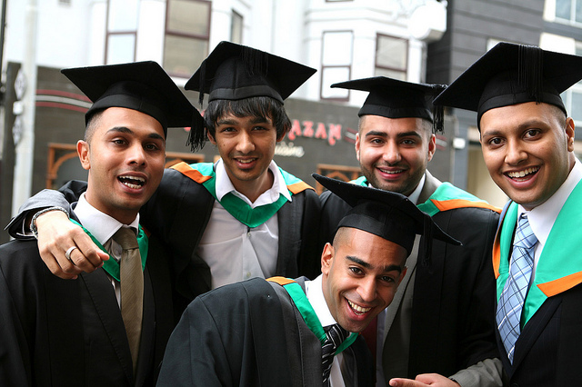Five young men in graduation gowns