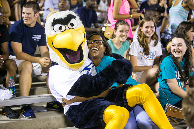 Photo of a Eagle mascot sitting on the lap of a woman in bleachers, while people around her smile
