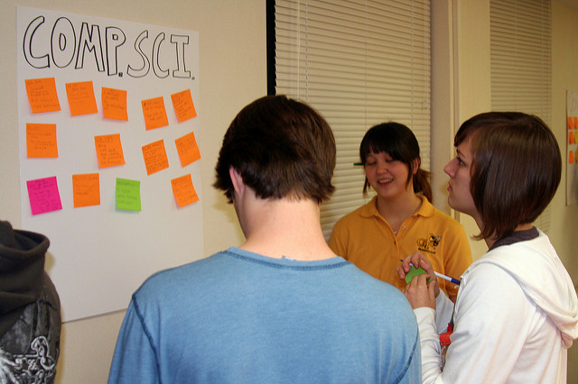 Photo of a group of students standing around a poster on the wall, where they're adding post-it notes with handwriting on them