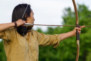 Person holding a bow with an arrow in position to release.