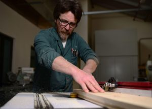 A man slides a long block of wood over a table equipped with tools to cut the wood.