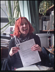 Woman sitting in office, holding a paper up to the camera and smiling broadly